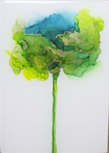 Abstract flower created with alcohol inks in greens, blues, yellows, and metallic gold.